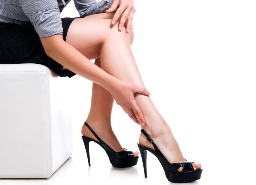 woman feeling her legs as if painful with varicose veins
