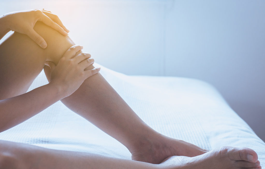 A woman with varicose veins sitting on her bed while caressing her left leg